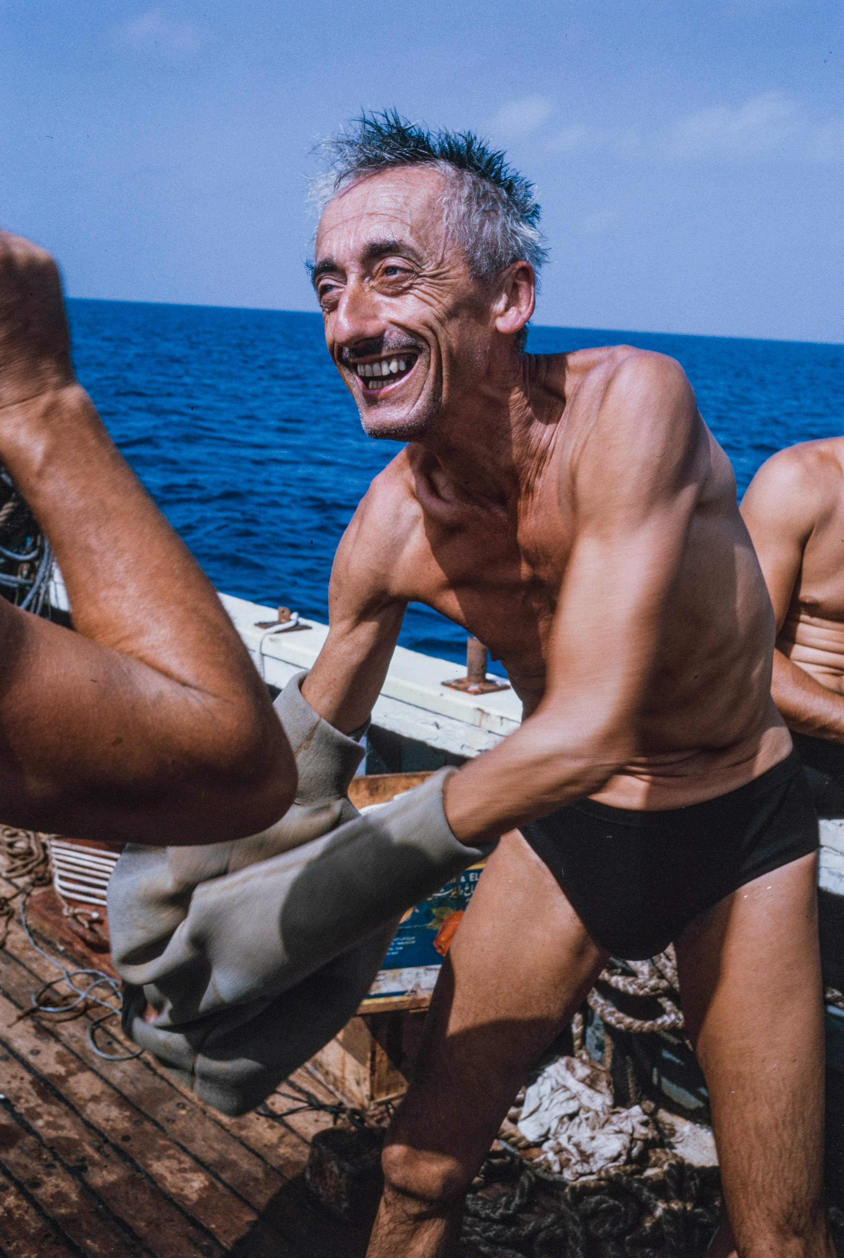 An elderly Jacques Cousteau smiles broadly as he peels off a wetsuit on board a boat at sea, with two other crew members just out of frame.