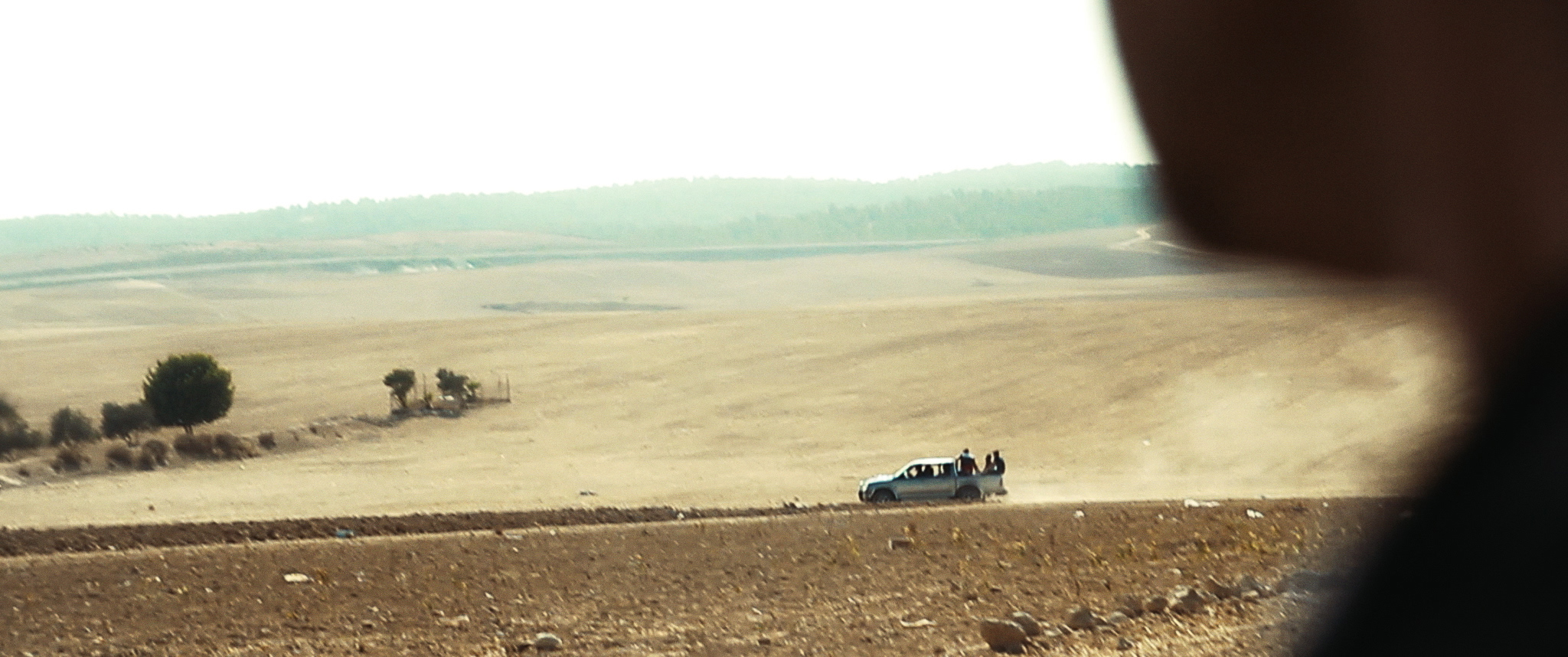 From the POV of a blurred figure in the foreground, a blue truck carrying five men drives along a dusty Palestinian road.