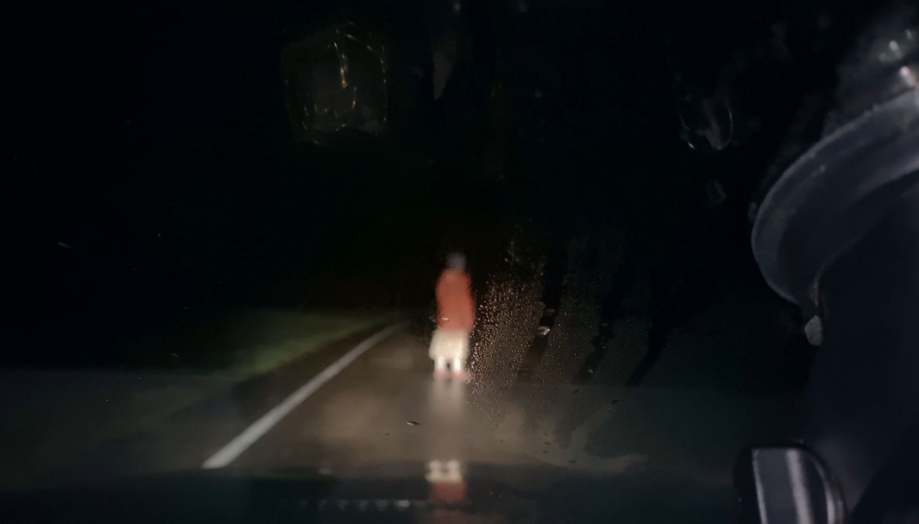A blurred figure wandering across a highway at night wearing a long orange sweater can be seen through the wet windshield of a car.