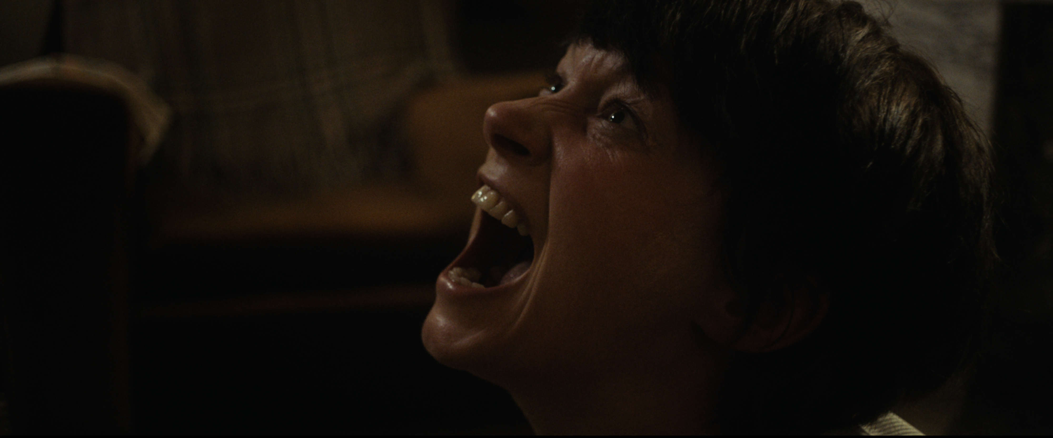 A close-up of Hazel Doupe screaming in a dark room.