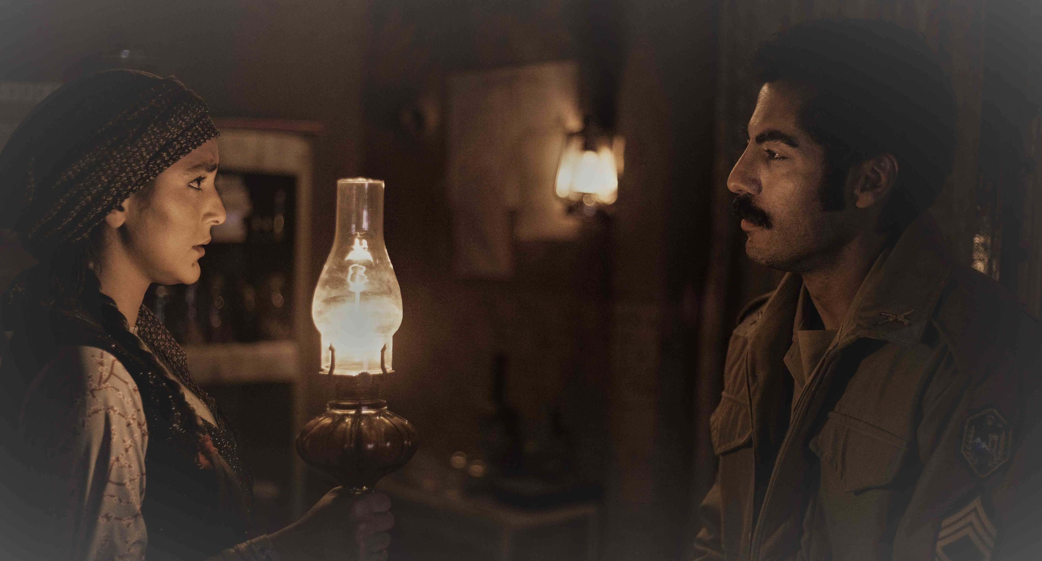Wearing traditional Iranian clothing, Hoda Zeinolabedin holds a lantern in a dark living room while speaking to Navid Pourfaraj in a military uniform.
