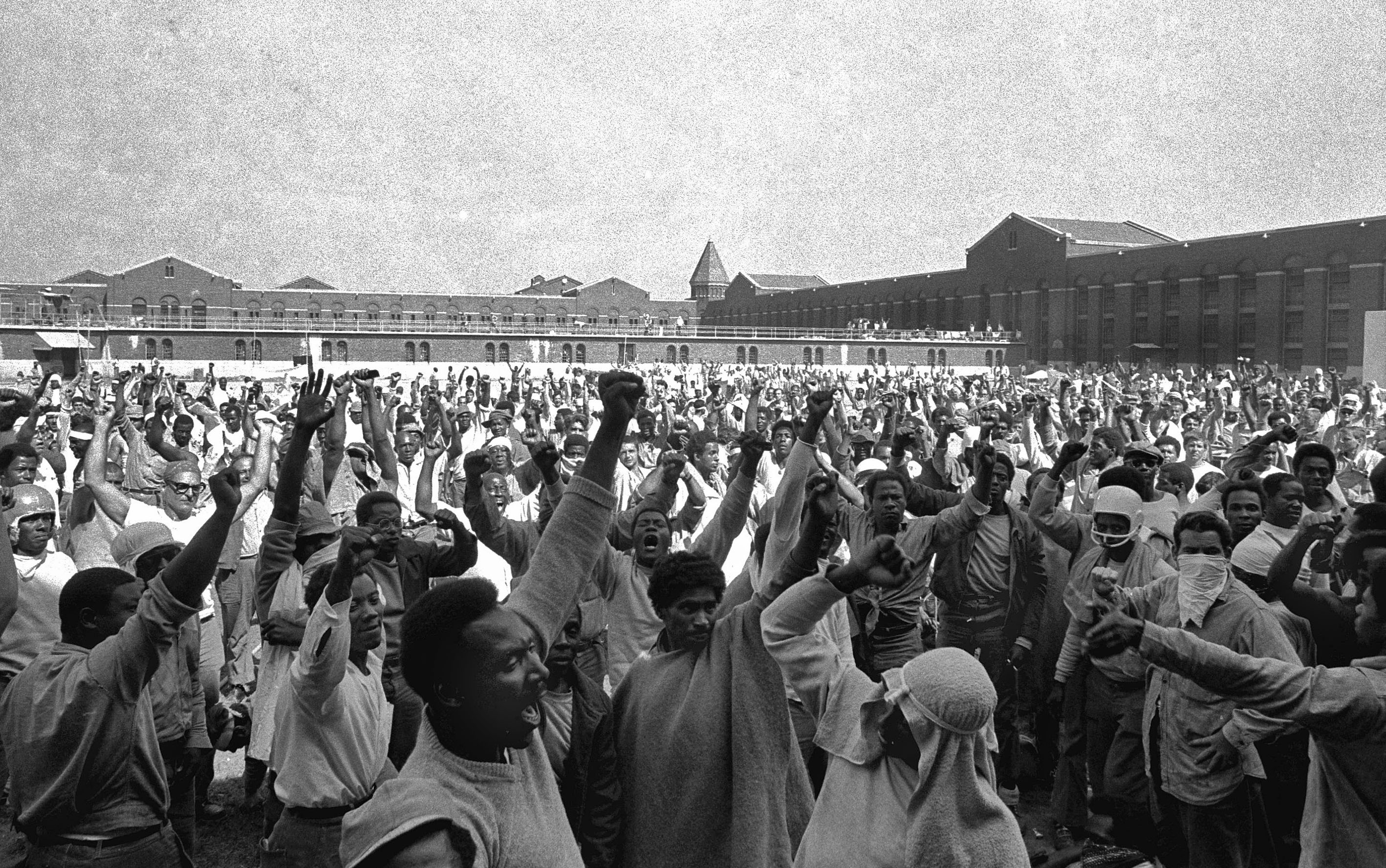 Inmates in a large prison yard raise their fists and yell together.