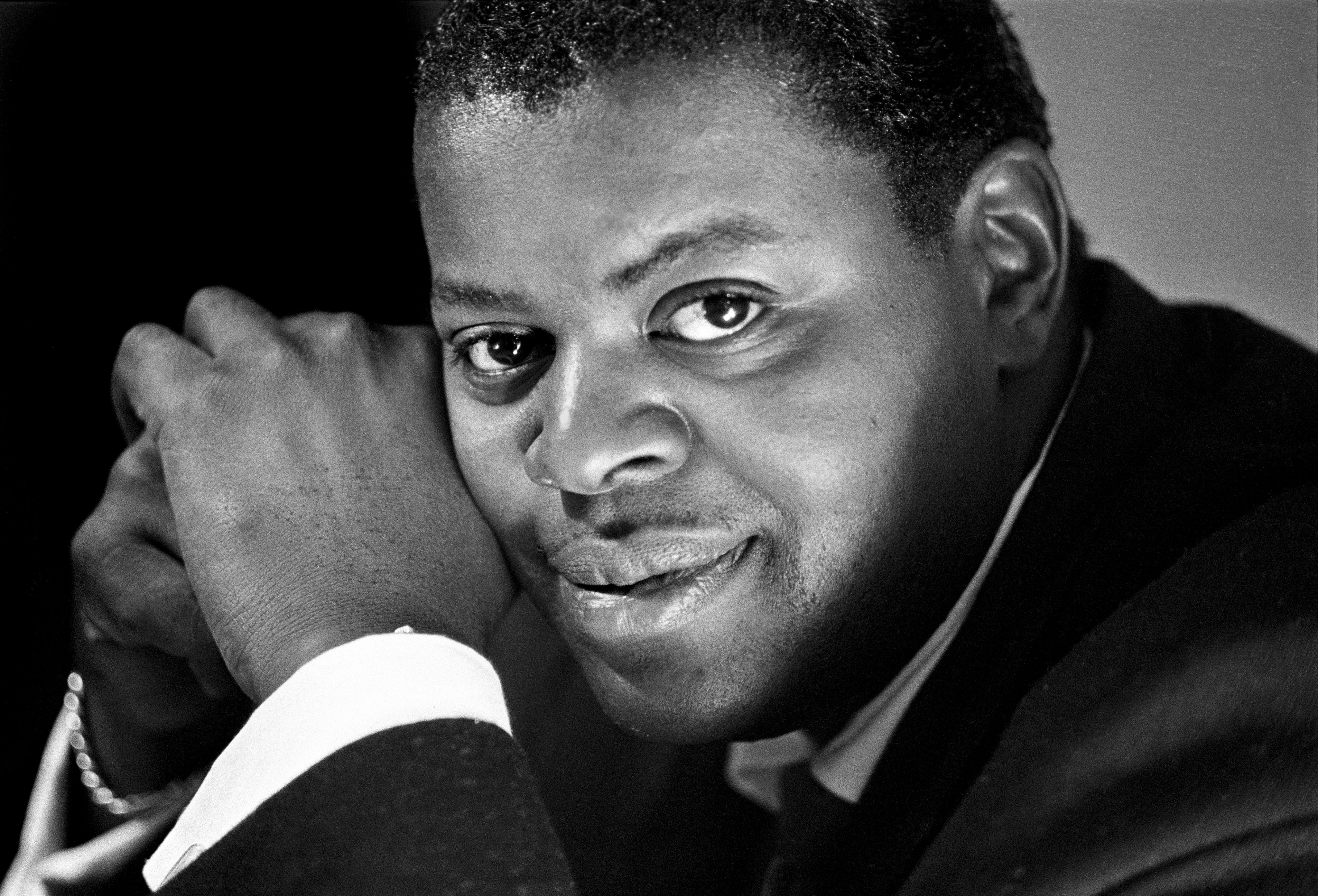 A black-and-white shot of pianist Oscar Peterson resting his face on clasped hands while looking beguilingly at the camera.