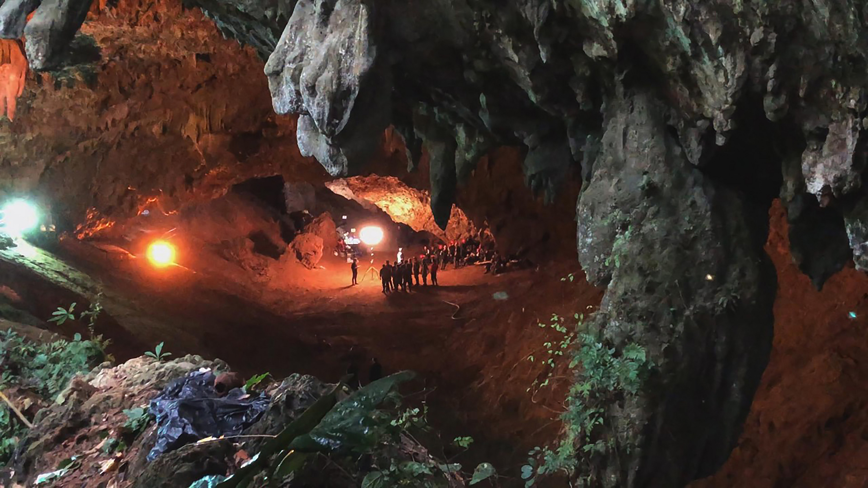 A pulled-out shot of a rescue team assembled in a Thailand cave, lit by one floodlight and dwarfed by large rock formations.