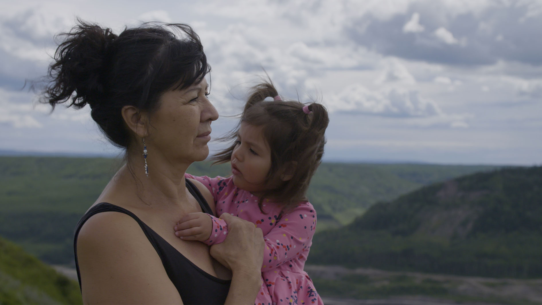 An older woman holds a small girl in her arms with green mountains behind them.