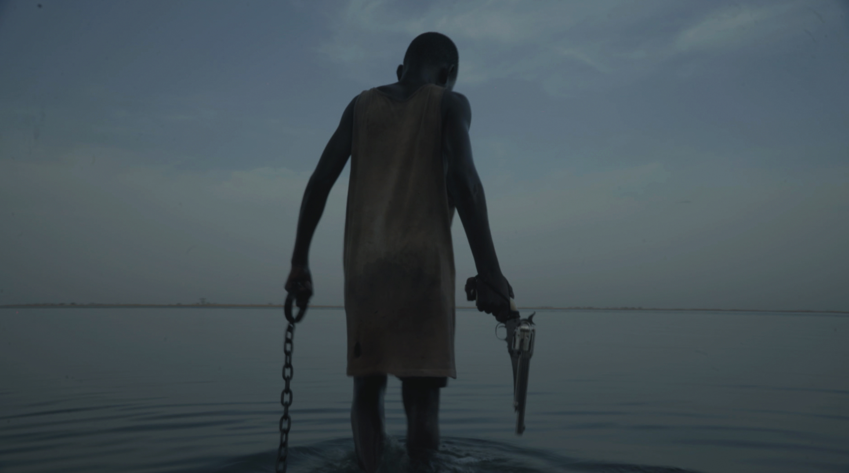 A person with a shaved head wearing a plain shift is seen from behind, ankle-deep in a bay holding a cuffed chain in one hand and a large revolver in the other.