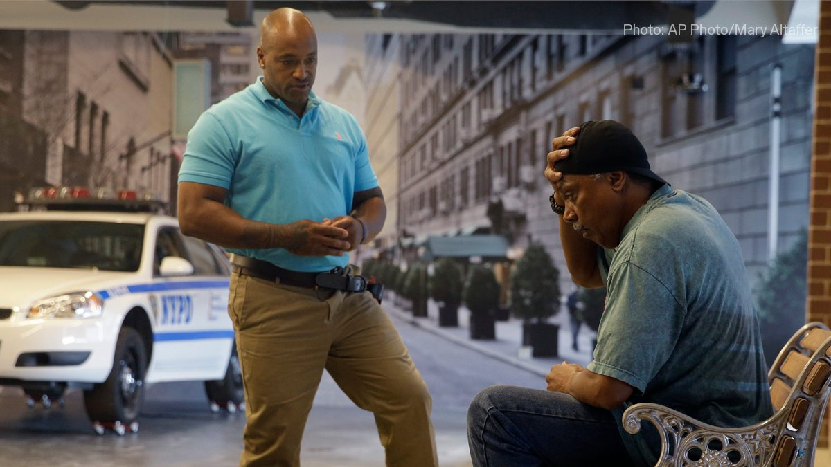 Image shows a New York City police officer talking to an actor during a Crisis Intervention Training class. The police officer is standing in front of the actor who is sitting on a bench with one hand on his head.