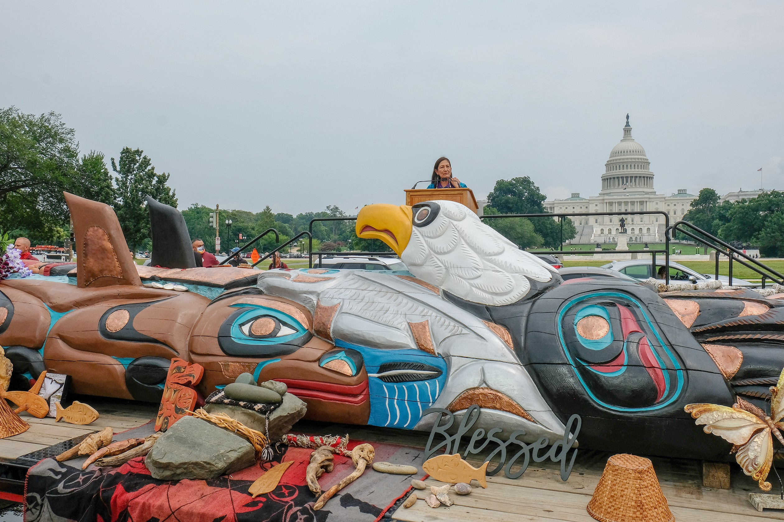 Secretary Haaland stands in front of the US Capitol Building with the totem in the foreground.