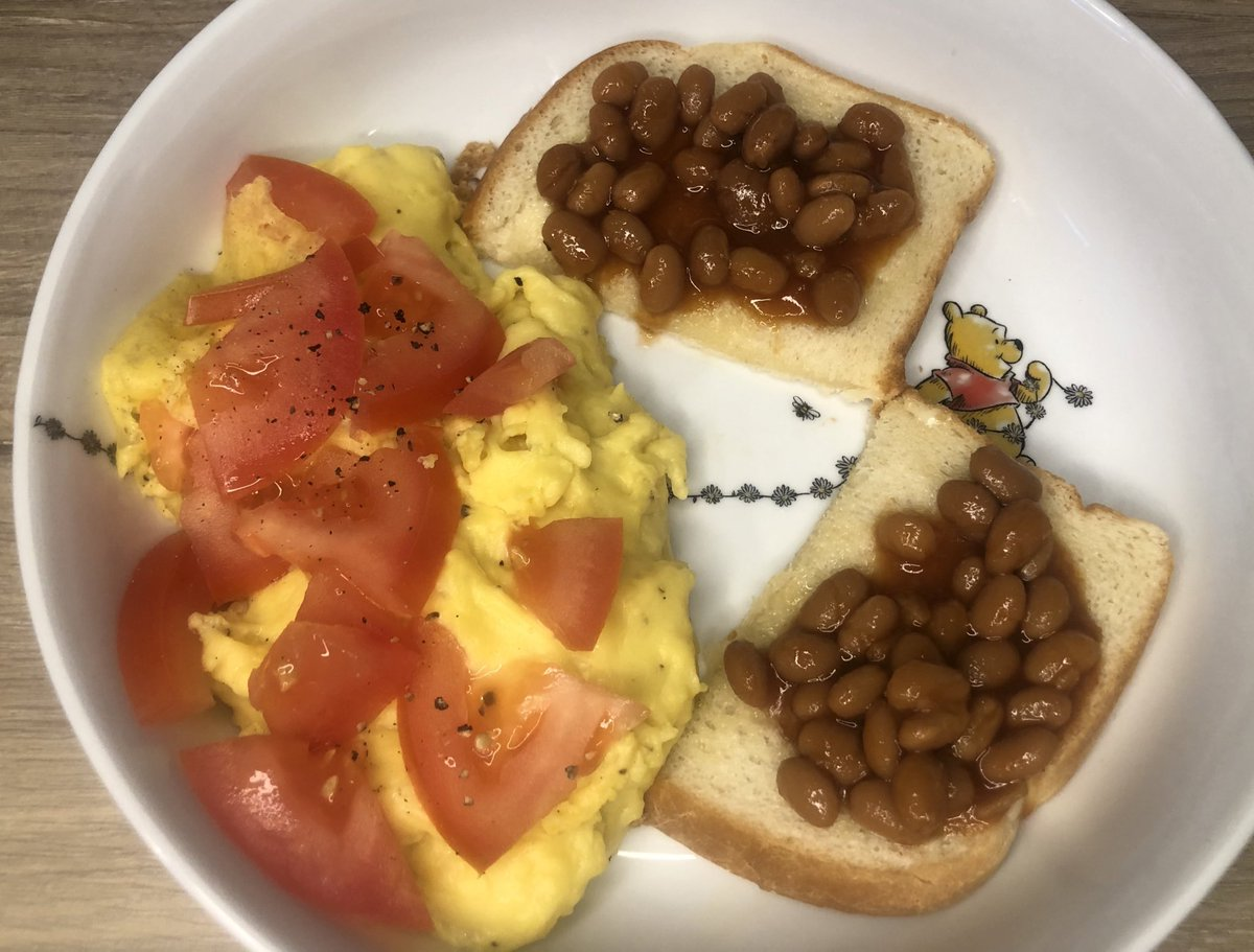 Aerial view of scrambled vegan eggs topped with tomato nestled on the sides by toast with baked beans, arranged triumphantly on a ceramic winnie the pooh plate.