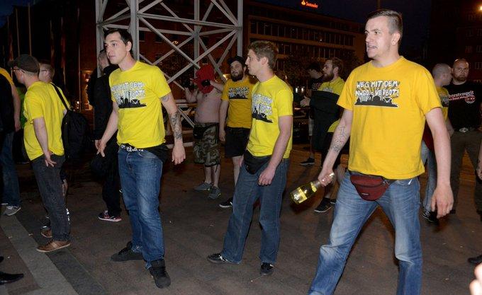 """Nazis mit gelben """"Weg mit dem NWDO-Verbot"""" stehen vor dem Rathausplatz. Lukas Bals hält eine Sektflasche am Flaschenhals fest (so als könne man damit gut zuschlagen)"""