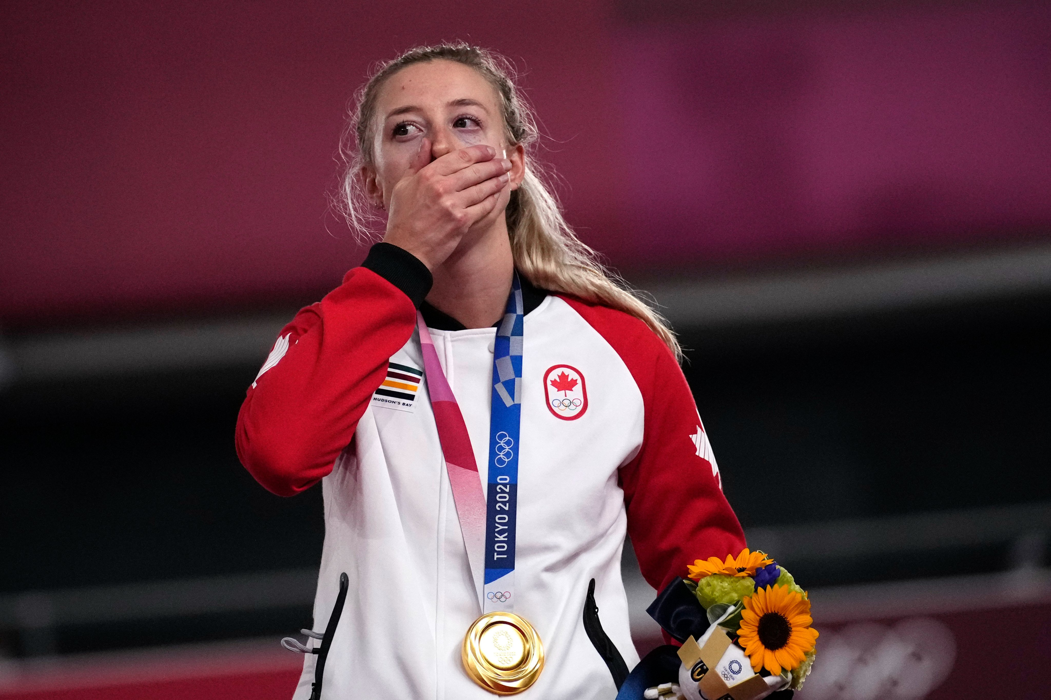 Kelsey Mitchell holds her right hand over her mouth while wearing her gold medal around her neck. She is holding podium flowers in her left hand.