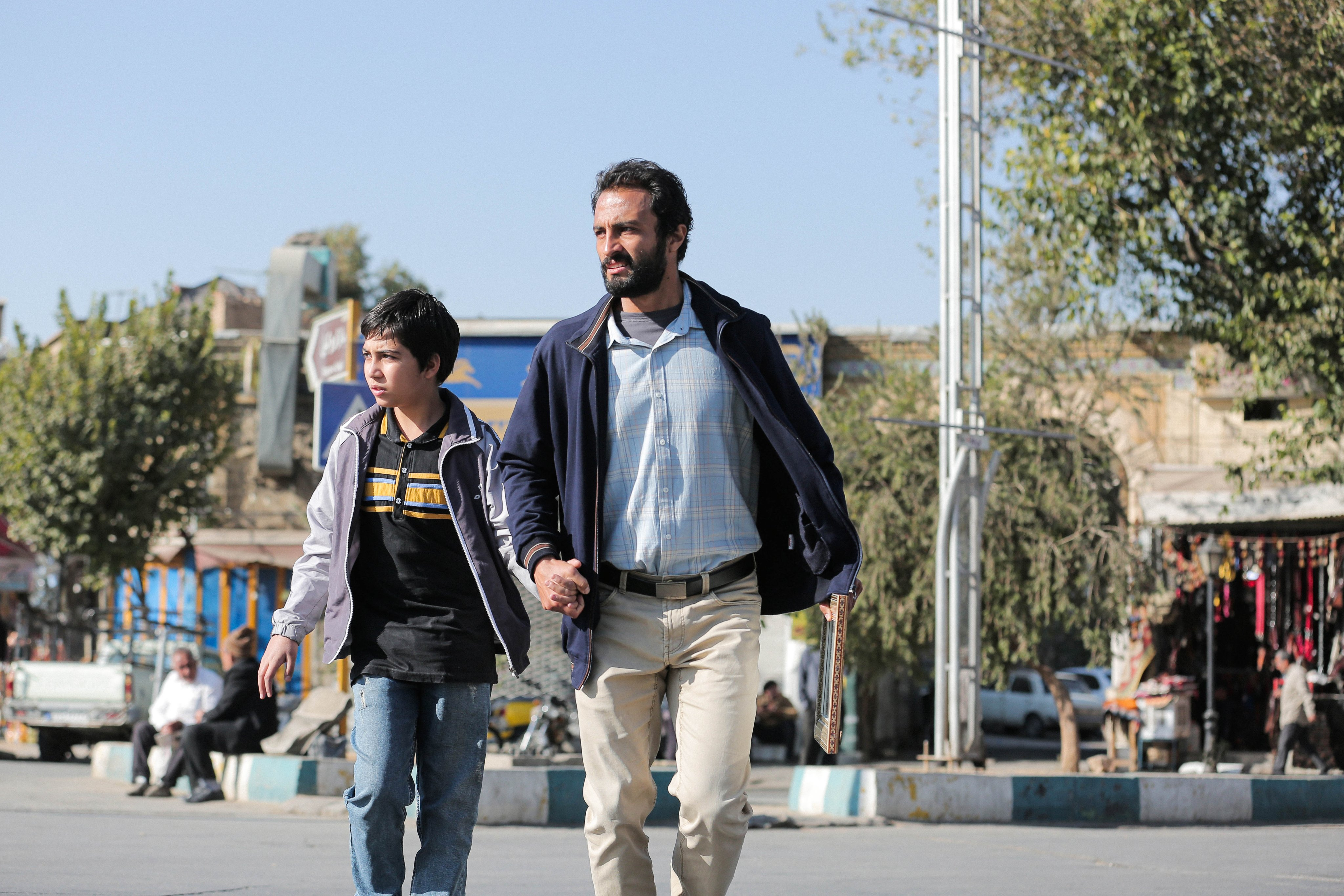 Amir Jadid holds the hand of a young boy as they walk around a plaza in the daytime.