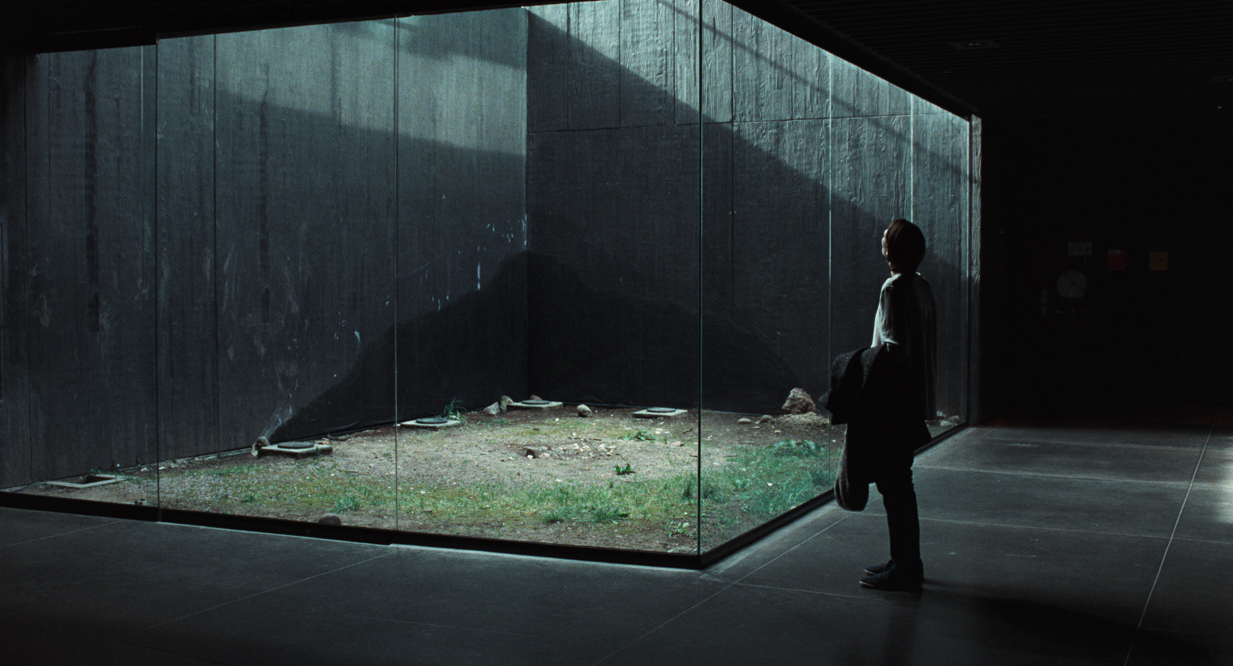 A woman in a dark room looks through a cubed glass window leading to an enclosed piece of land while holding a black piece of clothing.