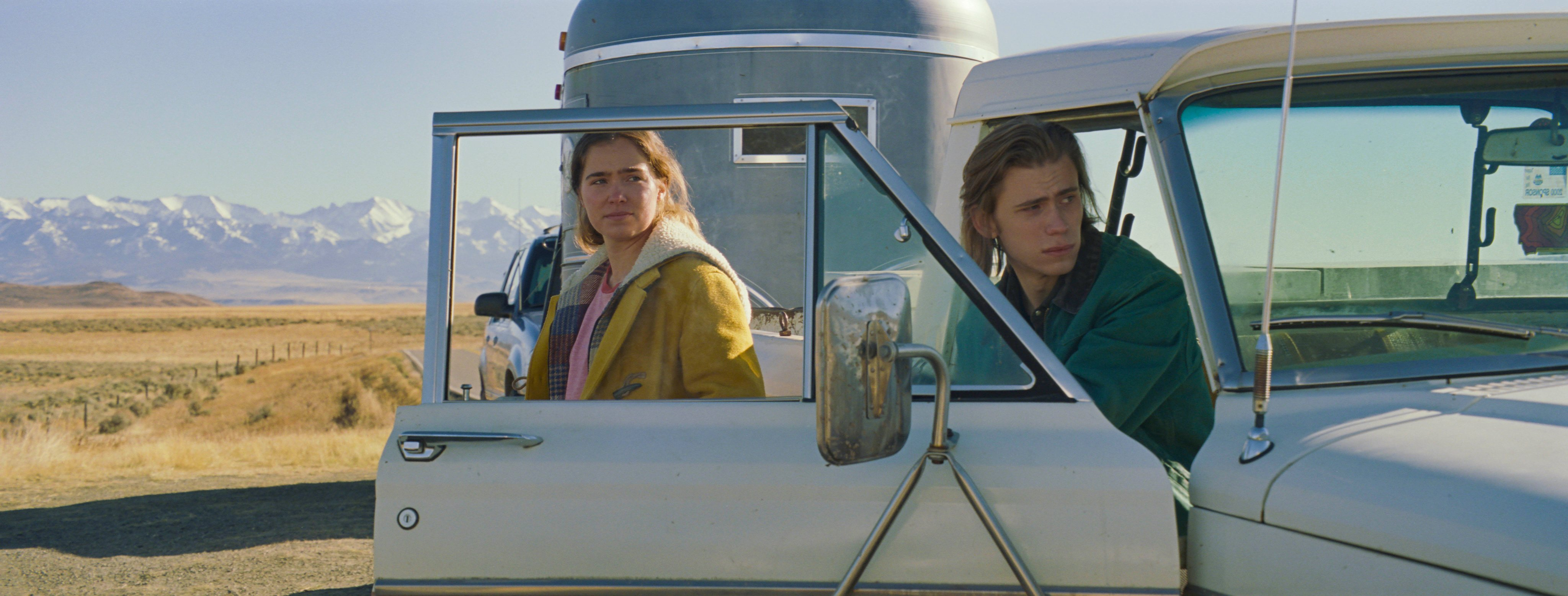 Haley Lu Richardson stands next to Owen Teague sitting in a white pick-up truck with the door open, in a field with a blue silo behind them.
