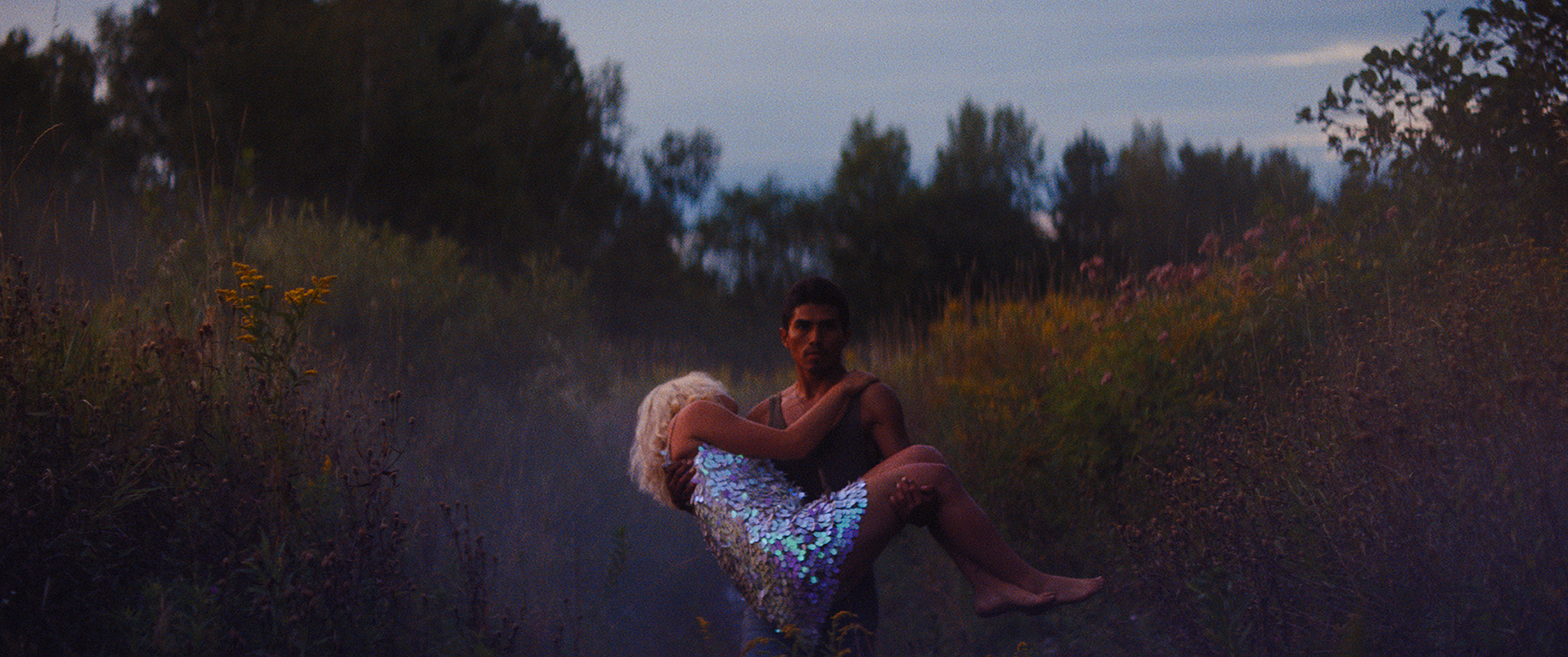 Jorge Antonio Guerrero in a grey tank top walks through a field of flowers, carrying a dazed woman wearing a short sequin dress.