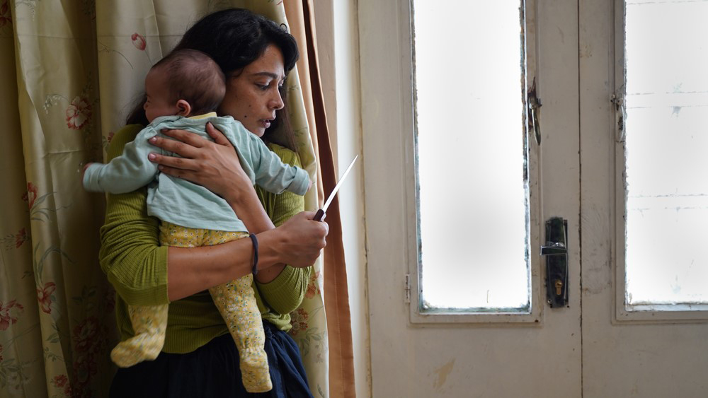 Maisa Abd Elhadi clutches a baby in her arms as she holds a knife and hides behind a brown-green curtain and a white windowed-door.