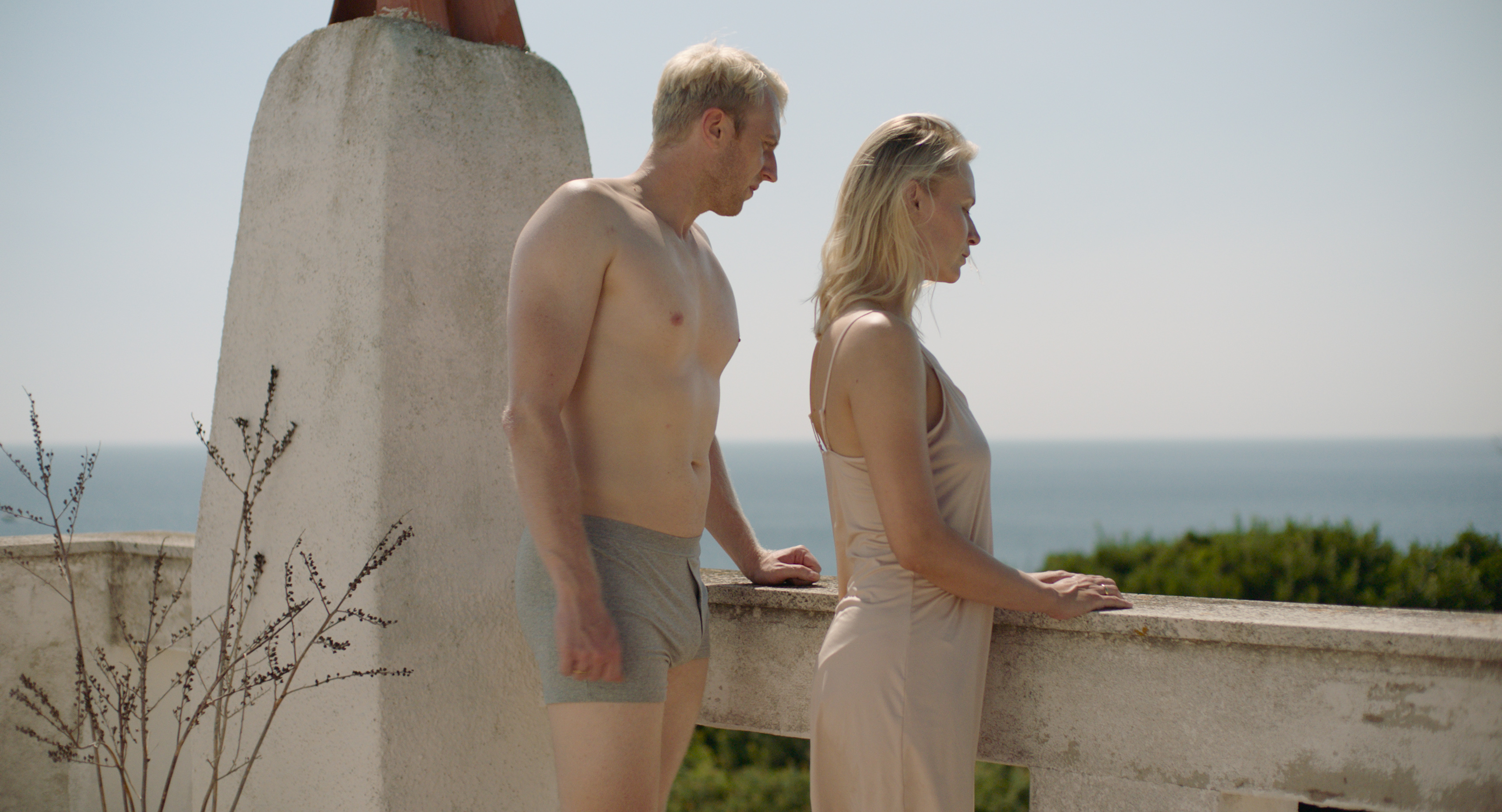 Dobromir Dymecki in grey boxers and Agnieszka Zulewska in a cream nightgown stand on a stone balcony, looking out into the distance.