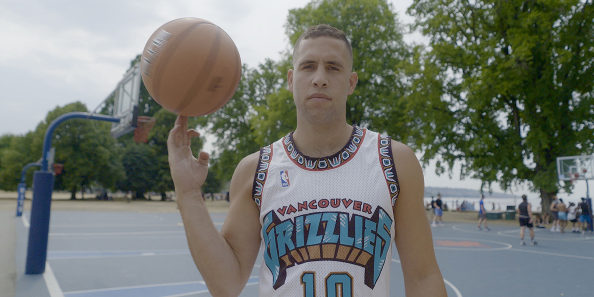 A man stands on an outdoor basketball court wearing a Vancouver Grizzlies jersey and holding a basketball.