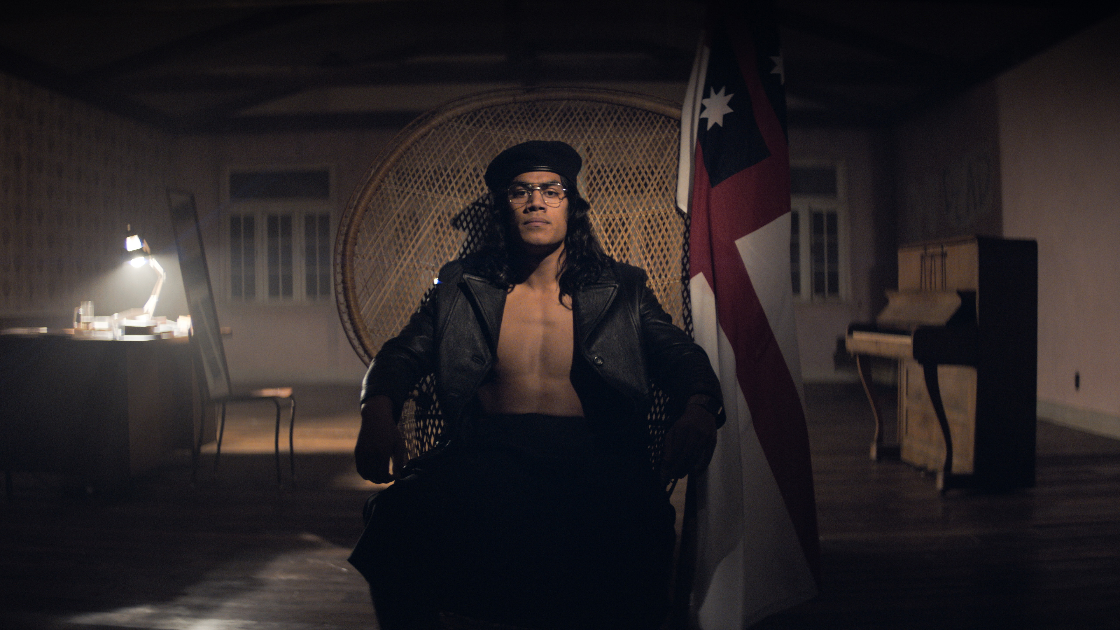 Seated on a wicker chair in a dimly-lit room, Dimitrius Schuster-Koloamatangi bears his muscular chest underneath a dark outfit with an open leather jacket. A flag leans beside him against the chair. Behind him from left to right is a desk with typical clutter and a lit office lamp, a wooden chair with a full-length mirror on top of it, and an upright piano.