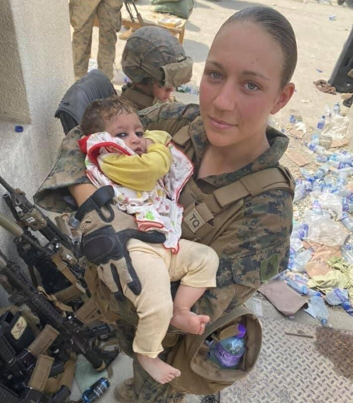 """One of the last photos that Marine Sgt. Nicole Gee shared with her family from #Afghanistan shows her hands in tactical gloves cradling a baby. In a short message posted with the photo, the sergeant said, """"I love my job🤘🏼"""" #kabul #Kabulairport #AfghanistanDisaster #KabulAttack"""