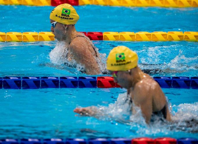 Foto das irmãs Beatriz e Debora nadando a prova de 100m peito. Elas estão bem próximas, mas Beatriz segue um pouco na frente.