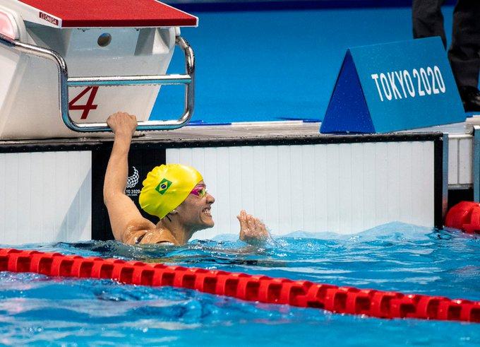 Foto da Maria Carolina Santiago dentro da piscina, segurando a raia com uma mão e sorrindo.