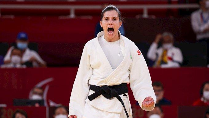Foto da Alana Maldonado com a boca aberta, enquanto celebra a vitória com o punho fechado, em sinal de força.