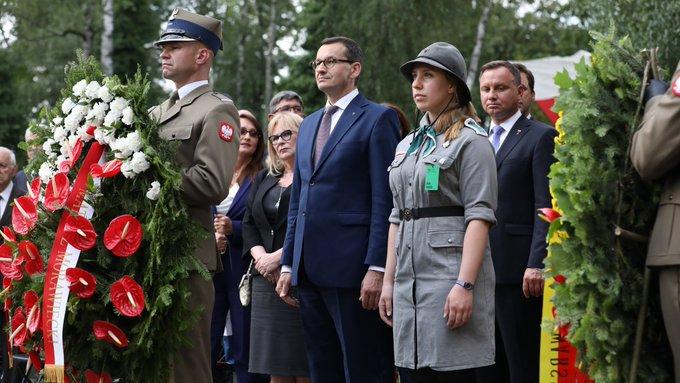 Premier stoi, przed nim żołnierz z wieńcem.
