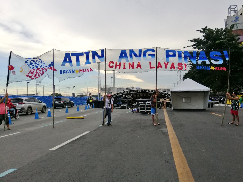 "LOOK: Early birds to the United People's SONA opposition rally at Commonwealth Avenue carry a banner declaring ""Atin ang 'Pinas! China layas!""   The fishnet-inspired banner also has a fish figure in the PH flag colors 