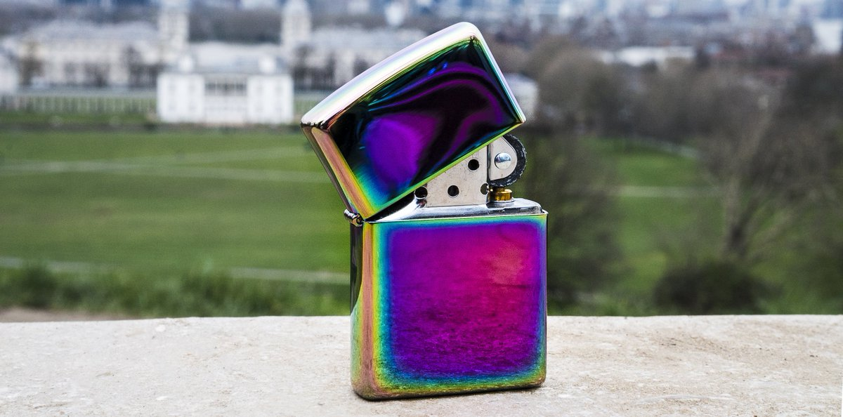 b240201b8ecdff A Zippo lighter with a MultiColor finish stands on a ledge.