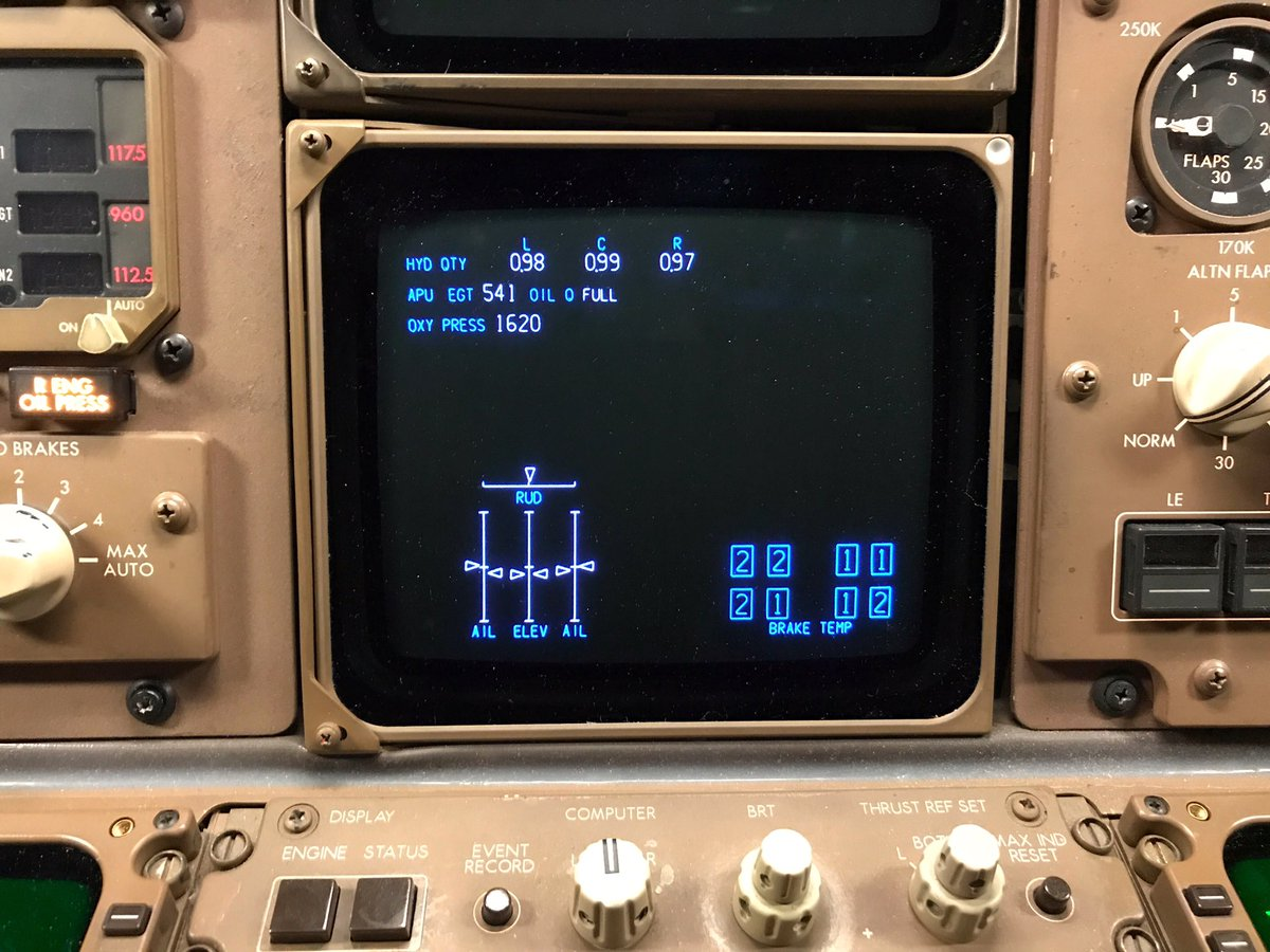 Lower center CRT display in a 767 cockpit. BRAKE TEMP display shows 2 sets of 4 light blue boxes. Each set represents a main gear with 4 wheels.   Each box contains a number representing temperature of wheel brakes. Left gear brakes indicate 2,2,2,1. Right gear indicates 1,1,1,2.