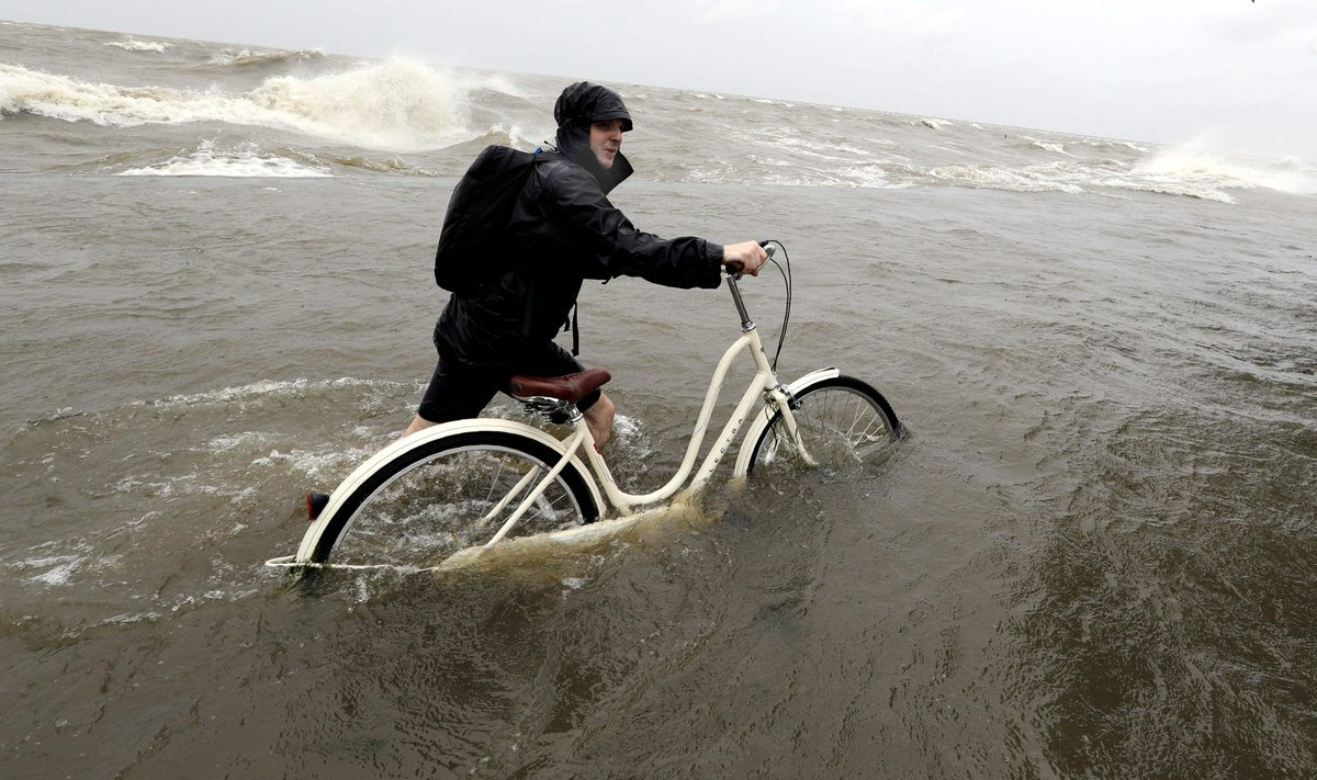 Tyler Holland guides his bike through the water as winds from Tropical Storm Barry push water from Lake Pontchartrain over the seawall, July 13, 2019, in Mandeville, La.  Photo: AP <br>http://pic.twitter.com/hsm0aDVgk6
