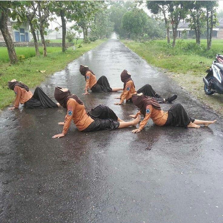 Sekelompok remaja putri berseragam Pramuka ini mungkin ingin memberi sesuatu yang berbeda dalam menikmati hujan