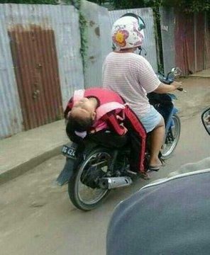 Waduh, sejujurnya ini bahaya. Si bocah benar-benar terlelap dalam tidurnya di atas motor yang bergerak.