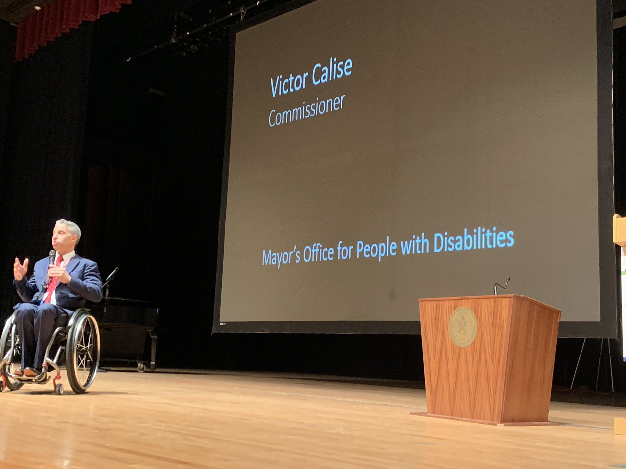 Victor Calise in a wheelchair on stage speaking beside a wheelchair podium