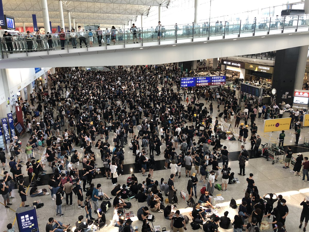 Airport sit-in continues. Fewer people than yesterday but still a strong showing. These were taken at around 2:30pm. #HongKongAirport <br>http://pic.twitter.com/0ffEtjqEc6