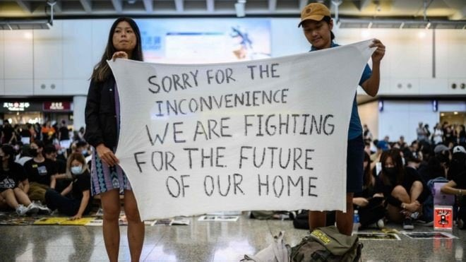 香港国際空港で見かけられた、旅行者への手書きの横断幕。「ご迷惑をおかけして申し訳ありません。私たちは故郷の未来の為に戦っています。」