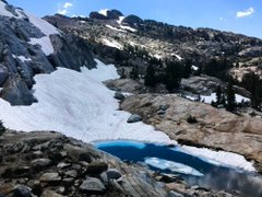 Rocky Mountain area with snow melting into a bright blue pool