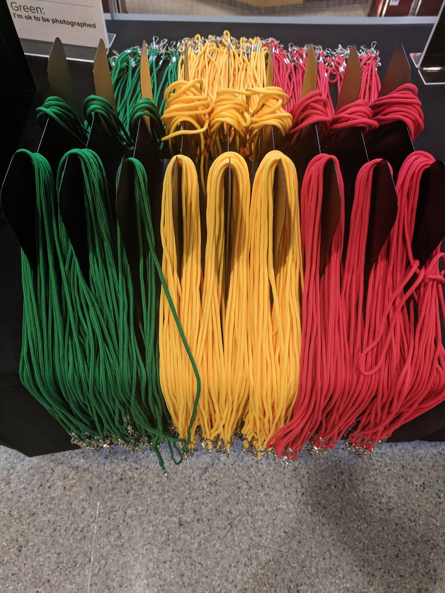 Numerous green, yellow, and red lanyards hanging on holders.