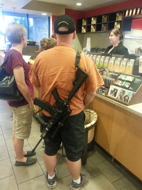 Man standing at a retail counter with a mass murder weapon strapped to him back, presumably in an Open Carry state.