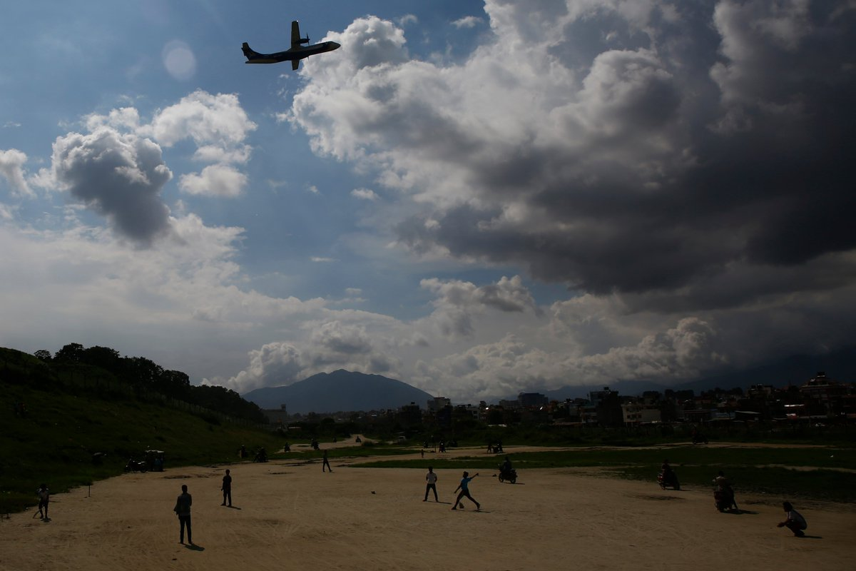 Youngsters silhouetted play cricket on an open ground as an aircraft takes flight in Kathmandu, Nepal on Saturday, August 10, 2019.