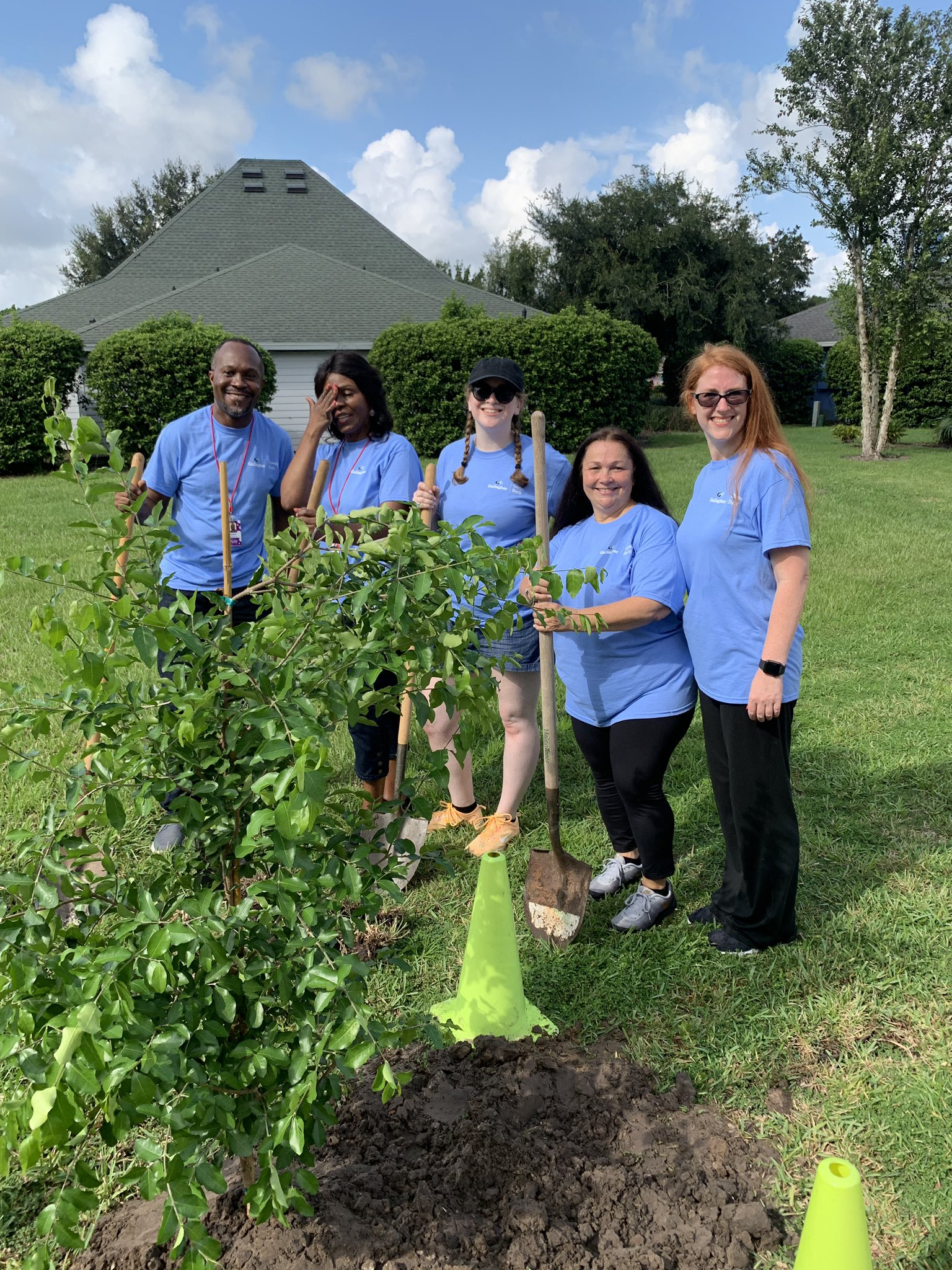 Rose Burford (Branch Manager) and her husband James, Andrea Humphries (Assistant Vice President), Alison Machulak (Assistant Branch Manager), and Megan Reed (Digital Marketing Lead) planting a tree.