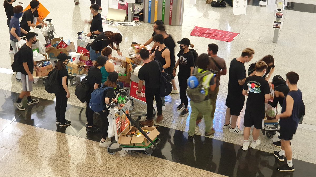"""At #Hongkongairport , with all the official personnel runaway, all shops and food stalls closed, the """"violent protesters"""" are distributing food and drinks for free to the waiting people. #standwithHK<br>http://pic.twitter.com/8gSBLW4Hy0"""