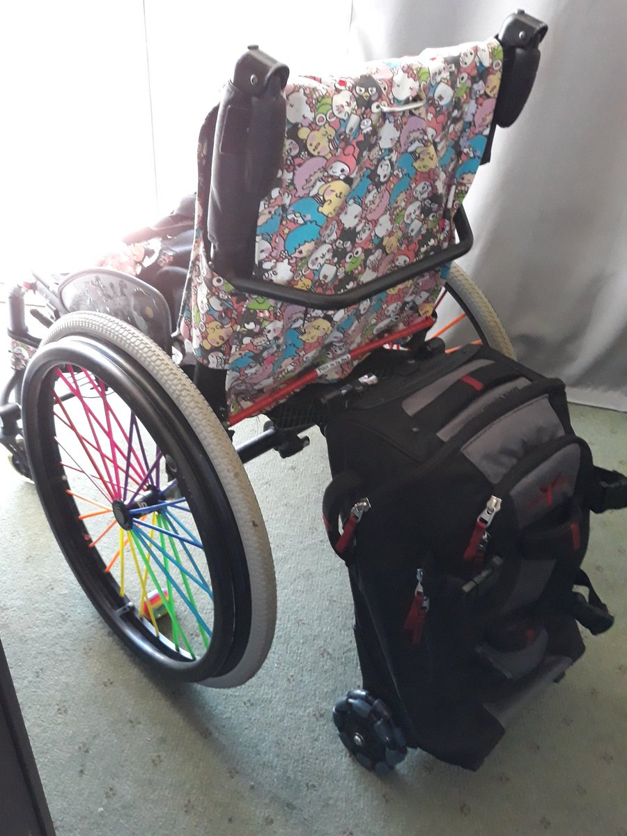 A manual wheelchair with rainbow spokes and colourful cover, with a black and red carry on bag clipped to the back of the chair.