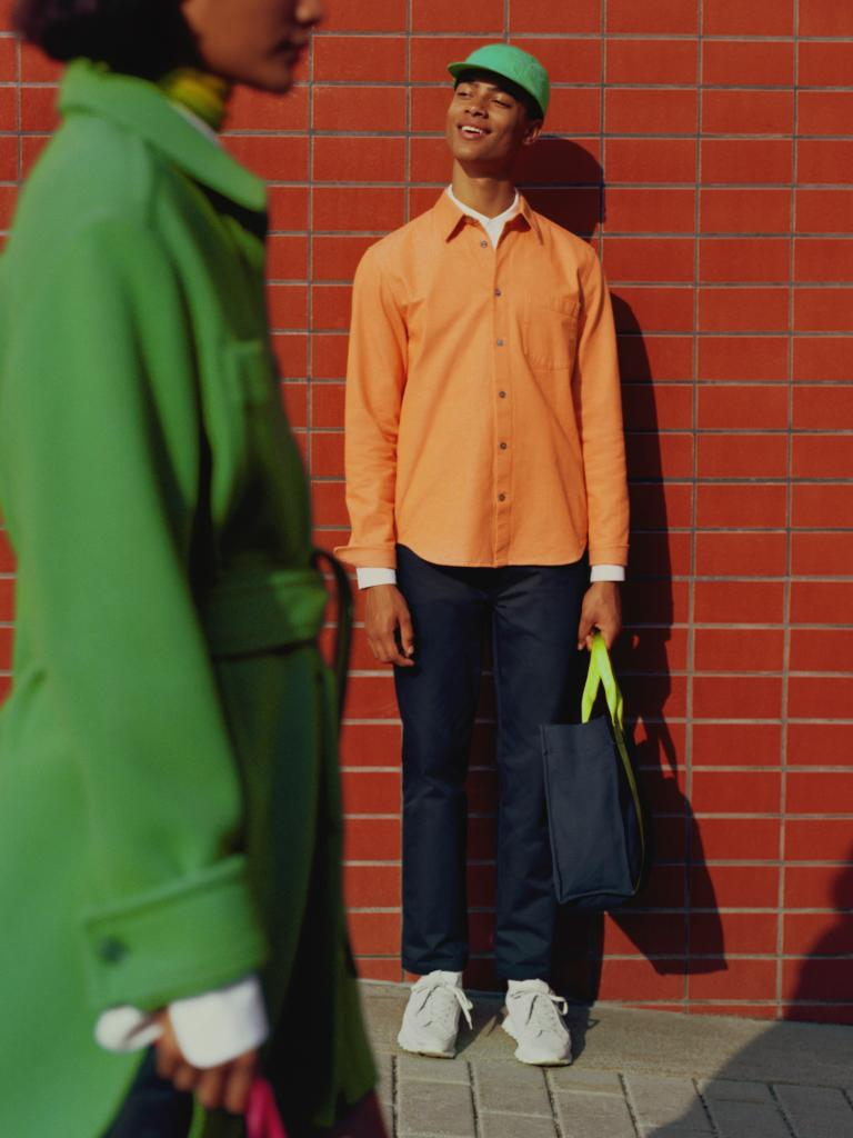 Male model standing against a brick wall carrying a bag and looking up at the sun.