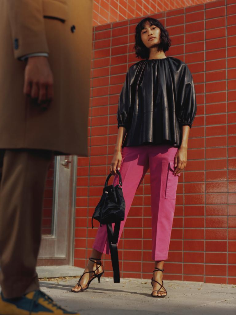 Female model by a brick wall standing with a bag. Male model in the foreground.