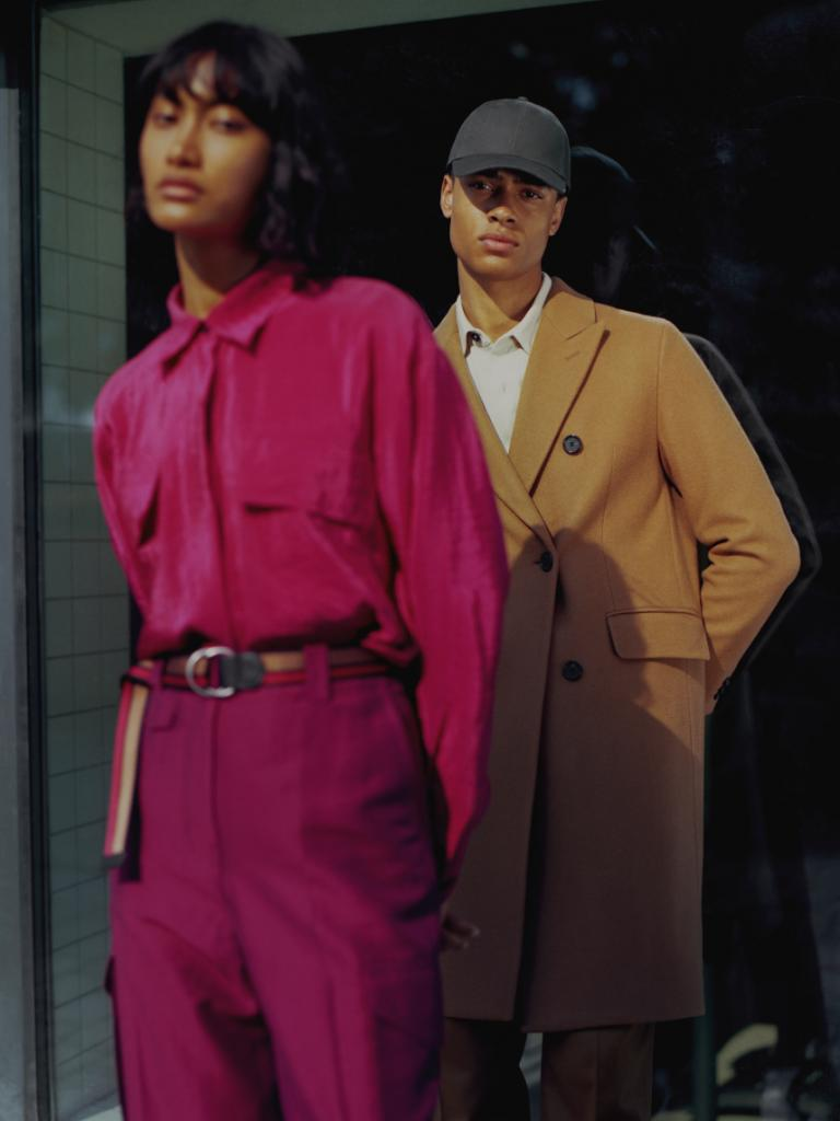 Male and female model standing together wearing pink and tan.