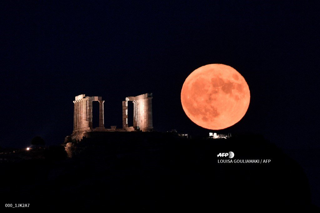 🇬🇷 The full moon rises next to the Poseidon Temple at the Cape of Sounion, some 70 km south of Athens. #AFP 📸 @lgouliam