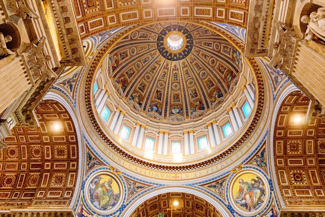 ミケランジェロ作の巨大クーポラの真下にはベルニーニ作の大天蓋。その更に真下がサン・ピエトロ=聖ペトロ、初代ローマ教皇のお墓になります。大天蓋の先の後陣には白い鳩のステンドグラスの下にペトロの司教座が。こちらもベルニーニの作品。