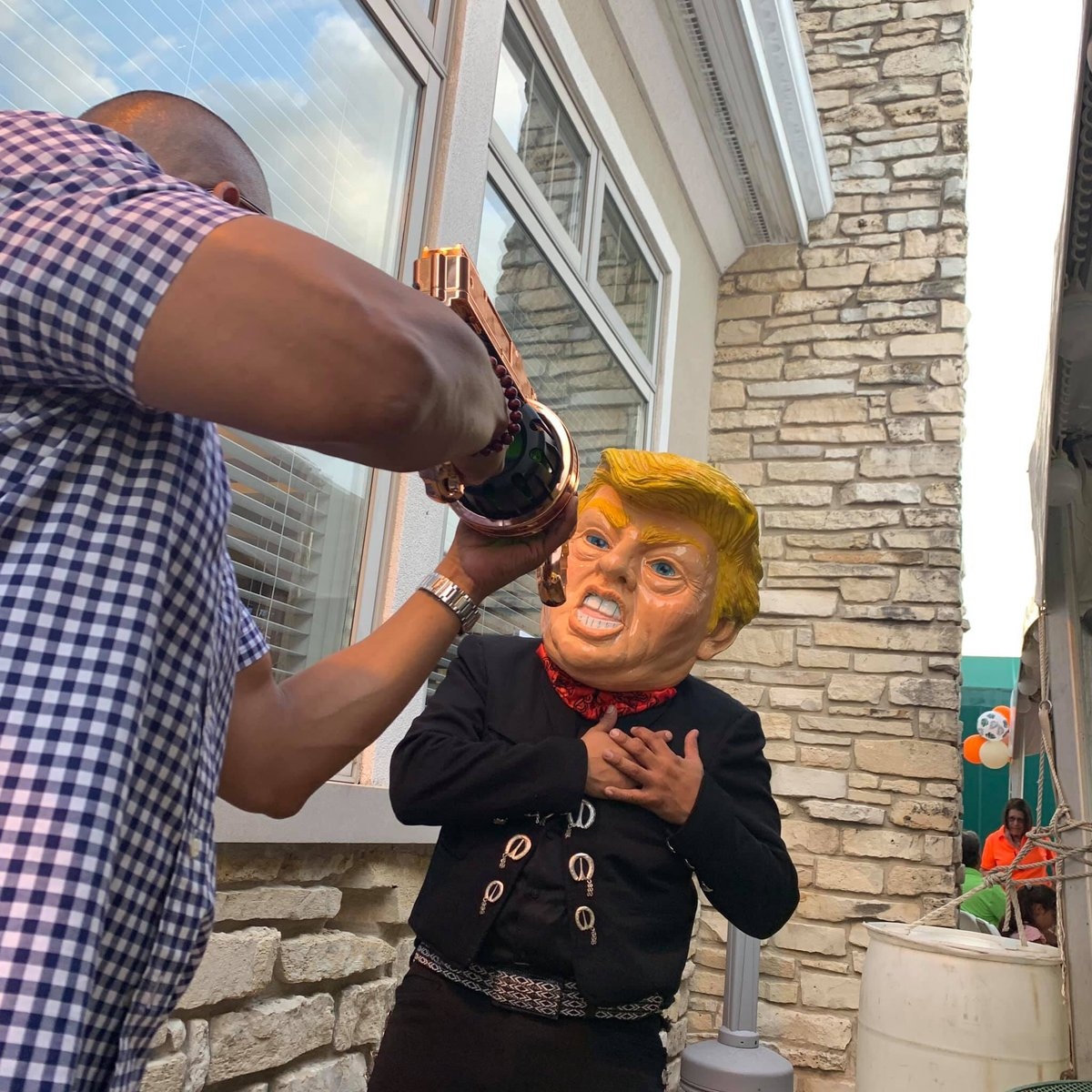 A political fundraiser for @SenatorSandoval simulates an assassination attempt against a mock @realDonaldTrump decked out in Mexican garb. Looks like a man pointed a fake assault weapon at the fake President to pose for a picture.